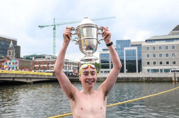Men's race winner Mark Hanley lifts the Liffey Swim Independent Cup (the trophy was donated by this newspaper in 1921). Picture: INPHO