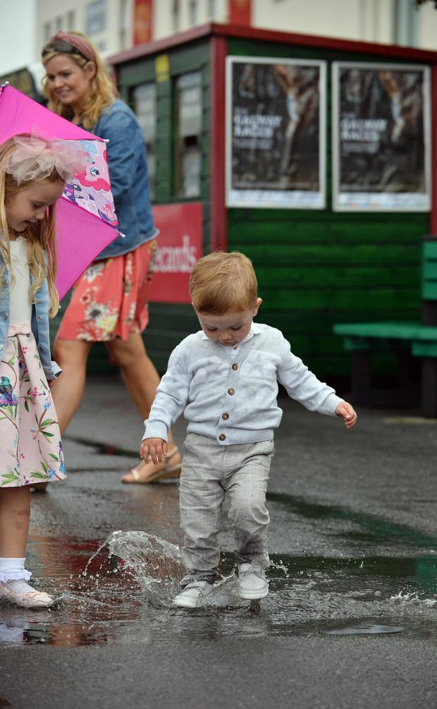Conor Mahon, from Co Offaly, splashes in a puddle at the Galway Races. Photos: Ray Ryan/Damien Eagers