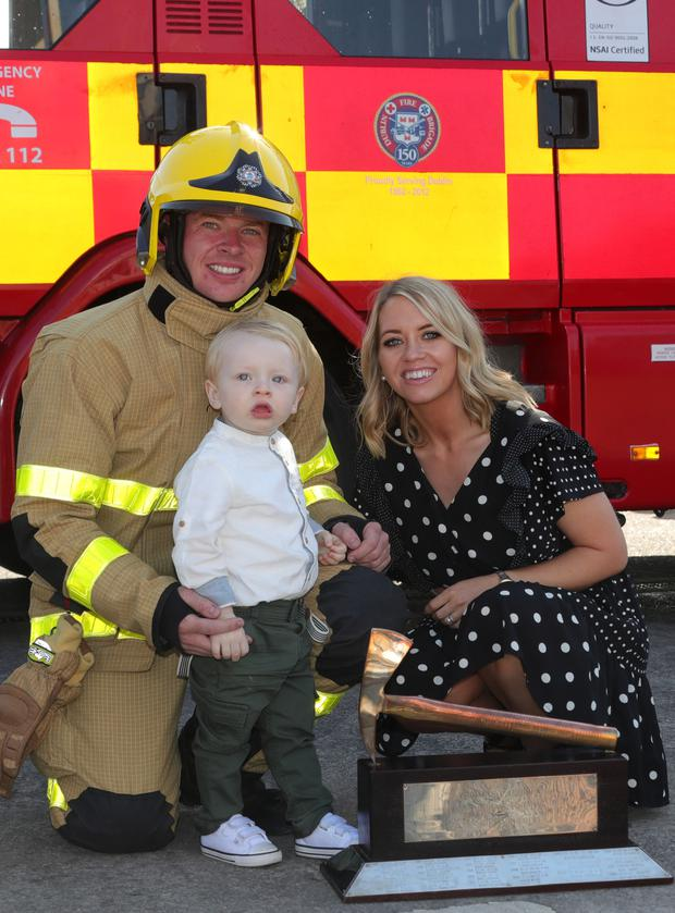 Family matters: Firefighter Derek Baitson, winner of the Silver Axe for best recruit in class, with his wife Claire and their son Bobby (2). Photo: Colin Keegan/Collins