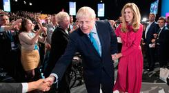 Speech: Boris Johnson leaves the stage with his partner Carrie Symonds. Photo: Stefan Rousseau/PA