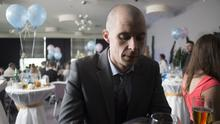 Tom Vaughan-Lawlor as Nidge at Warren's communion party*