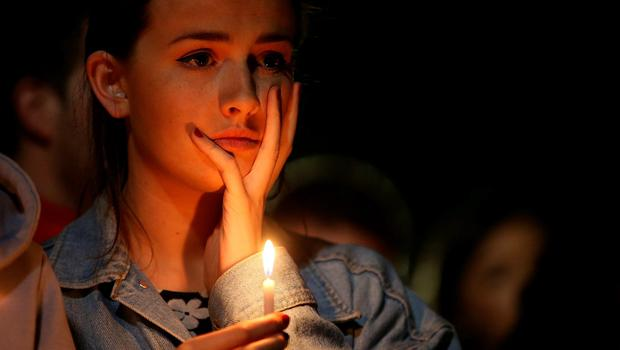A woman holds a candle during a candlelight vigil at the Martin Luther King Jr Civic Centre Park in Berkeley