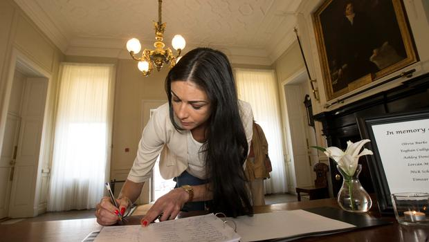 A woman signs a book of condolence at the Mansion House following the deaths of the young Irish students in the Berkeley tragedy