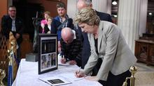 Former President Mary McAleese signs the book of condolence in St Mary's Pro Cathedral in Dublin after a special mass of remembrance and prayer at the weekend