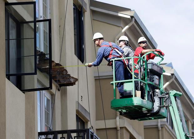 A worker measures near the remaining wood from an apartment building balcony that collapsed in Berkeley