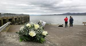 Flowers at the pier where the five people lost their lives in Buncrana, Co Donegal. Photo: Mark Condren