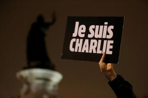"""A man holds a placard which reads """"I am Charlie"""" to pay tribute during a gathering at the Place de la Republique in Paris January 7, 2015"""