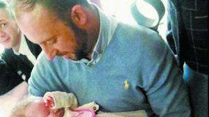 Rescue hero Davitt Walsh cradles baby Rioghnach-Ann, whom he saved from the icy waters. Photo:Derry News