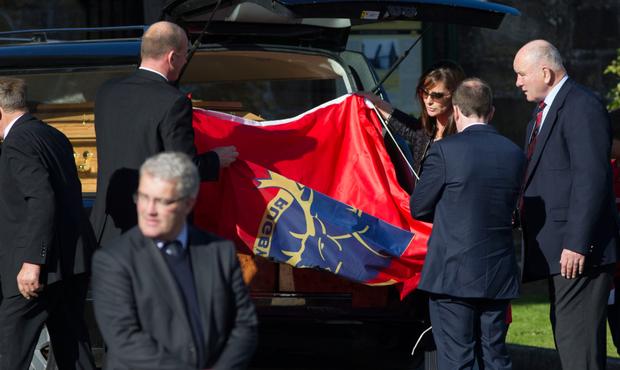 Brendan Foley looks on as Anthony's sister Rosie Foley takes the Munster flag off Foley's coffin Photo: Mark Condren