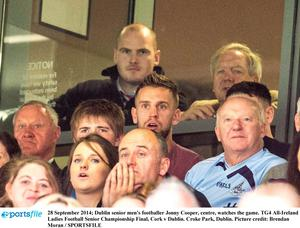 Dublin footballer Jonny Cooper, centre, watches the ladies' All-Ireland final between Cork and Dublin at Croke Park yesterday. He is still recovering from an unprovoked knife attack.