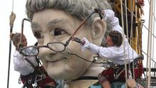 Performers from the French arts group Royal de Luxe adjust the spectacles of their giant grandmother puppet