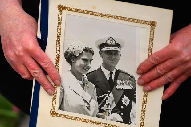 A person holds a photograph of Queen Elizabeth                   and Prince Philip outside Windsor Castle. PA