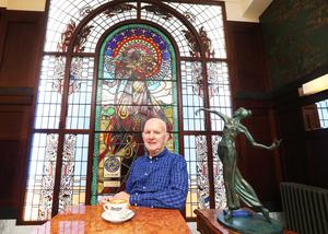 Bewley's owner Paddy Campbell sits in front of the café's iconic stained-glass panels. Photo: Leon Farrell
