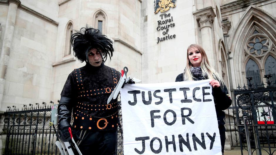 Supporters of actor Johnny Depp pose outside the High Court in London. Photo: Reuters/Toby Melville