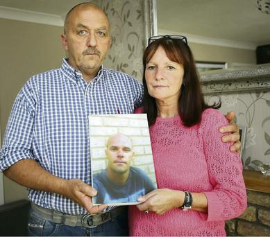Aidan and Catherine Greene with a photo of their son, David, who was murdered in Australia