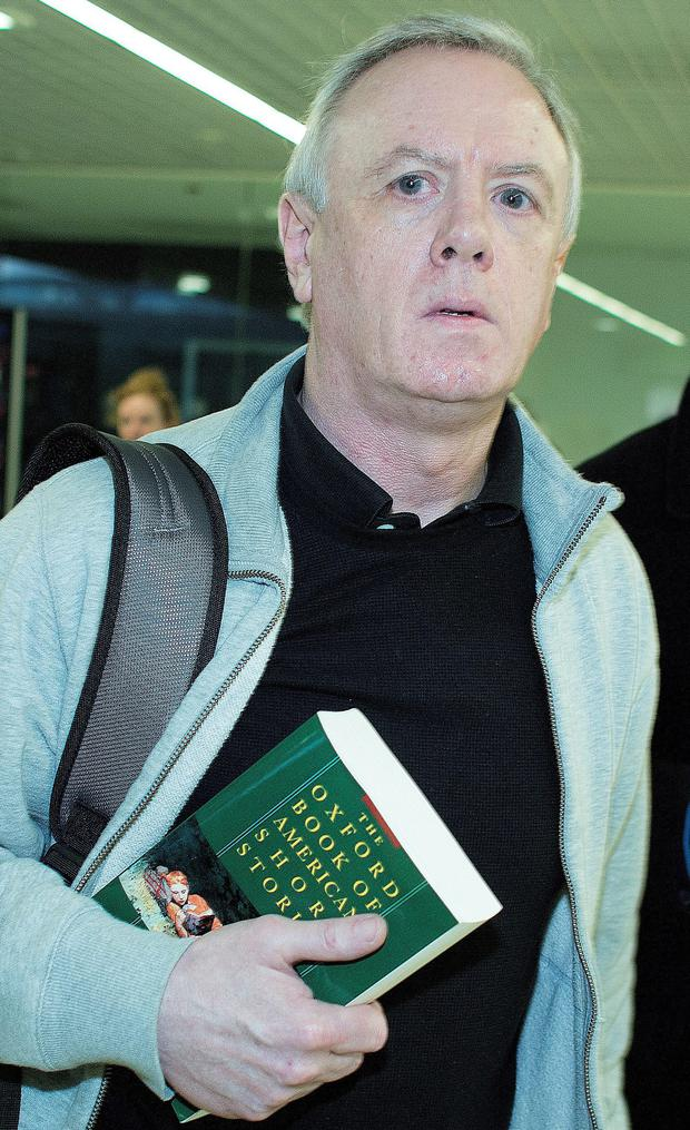 READING MATTER: Eamonn Lillis carries a book through Dublin airport yesterday. Photo: David Conachy