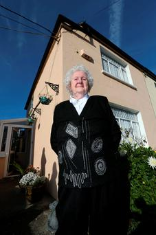 Anne Rudd in front of her home where the satellite dish was once fixed to the wall beside the alarm