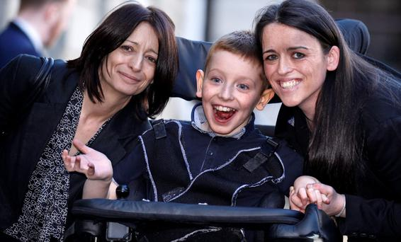 AWARD: Lee Gibson (10) with his grandmother Stephanie, left, and mother Aileen, right, outside the High Court on Thursday