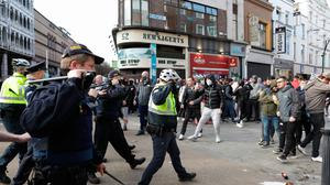 Gardaí face protesters in Dublin city centre on Saturday. Photo: PA