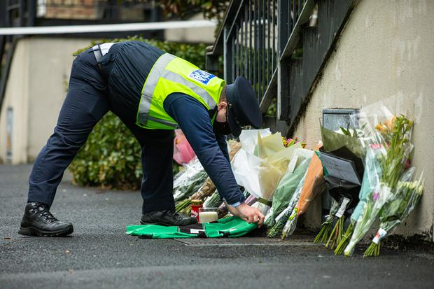 A member of An Garda Síochána lays an Erin's Isle GAA club jersey at Melville Drive, Finglas where Jennie Poole was found with fatal injuries. Photo: Mark Condren