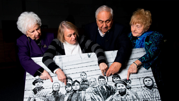 SURVIVORS OF HELL ON EARTH: Miriam Ziegler, Paula Lebovics, Gabor Hirsch and Eva Kor pose five years ago with the original image of them as children taken at Auschwitz at the time of its liberation. Eva Kor died last year, aged 85