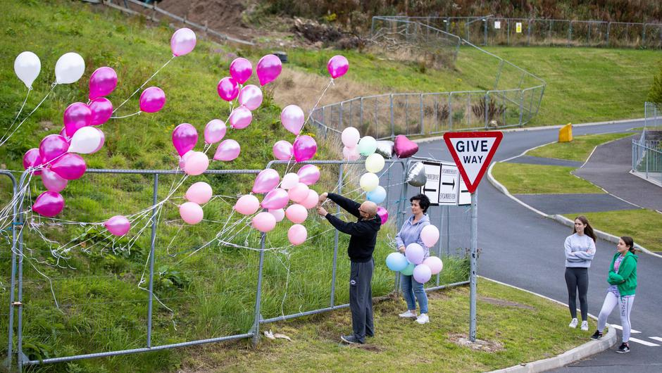 People attach balloons to a fence in remembrance during a vigil in Dungannon, Co Tyrone, for two-year-old for Ali Jayden Doyle who died in hospital on August 6. Picture: PA