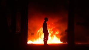A protestor stands near a burning car as police attend the scene at Cloughfern where loyalist protestors hijacked and burned vehicles on Saturday. Photo: Charles McQuillan/Getty Images