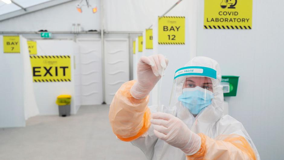 A lab technician with a swab at RocDoc's testing facility in the Blue Car Park of Dublin Airport for hauliers bound for France. The company have announced additional drive-thru testing services at Cork and Shannon Airports for hauliers arriving in cars. PA Photo
