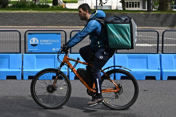 """A Deliveroo rider makes use of a new expanded cycle lane, """"streetspace for London"""" on Park Lane"""