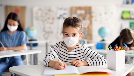 Stock image of a child with a facemask in school