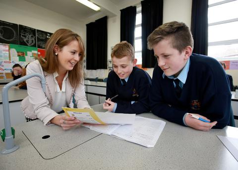 Newly qualified maths teacher Fiona Keary helps Our Lady of Mercy Secondary School Drimnagh students Jack Hartigan and Thomas McDonnell (13). Photo: Frank Mc Grath.