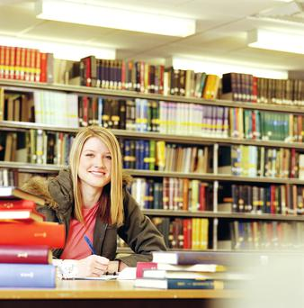 Female college student in library, smiling, portrait