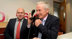 Education Minister Richard Bruton answers a call to the helpline, with NPCpp president Geoffrey Browne. Photo: Caroline Quinn