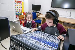 Grace Campbell and Liam Nolan doing their podcast in St Peter and Paul Primary School