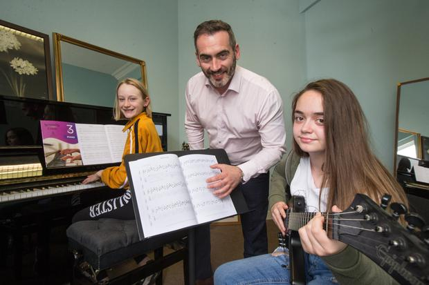 Craig Wynne, Director of the Academy of Modern Music, with budding musicians Alana Flood on piano and Charlotte Clinton-Murray on guitar. Photo: Mark Condren