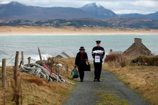 Presiding officer Carmel McBride and Garda Sergeant Paul McGee carry a ballot box away from a polling station after voting concluded on the island of Inishbofin. Photo: Niall Carson/PA