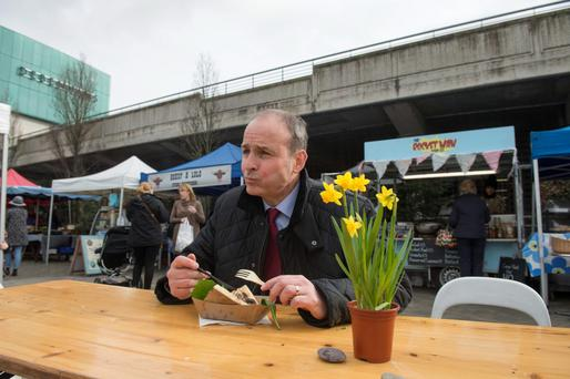 Fianna Fáil leader Micheál Martin enjoys a steak sandwich in Mahon Point in Cork yesterday. Photo: Michael Mac Sweeney
