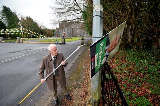 Diarmuid O Buachalla, returning officer for Galway East, cuts down election posters which were displayed too close to the voting centre in Mountbellew. Photo: Ray Ryan