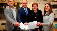 Fianna Fáil leader Micheál Martin casts his vote with son Micheál Aodh, wife Mary and daughter Aoibhe in Ballinlough, Cork. Photo: PA