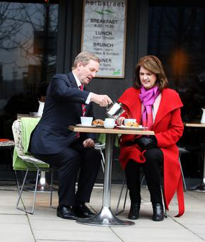 Taoiseach Enda Kenny TD pours the tea for Tanaiste and Labour leader Joan Burton,TD when they met for a cuppa in a cafe on Hanover Quay. Photo: Tom Burke