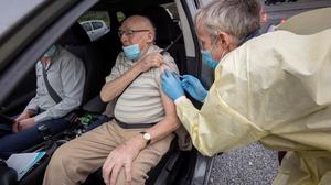 Chambers giving a vaccine to Bob McGarry in Kilkenny, completing prep work between jabs, and approaching a car to administer another dose of the vaccine. PHOTO: DYLAN VAUGHAN