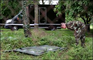 Landing site: A member of the Air Corps inspects the door that fell into the grounds of Moyle Park College in Clondalkin. Photo: Steve Humphreys