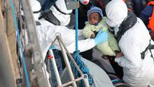 A baby is rescued from a small craft by the crew of the LÉ Eithne yesterday.