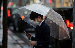 What's up, WhatsApp? A man, wearing a protective face mask scrolls through his phone in Tokyo this week