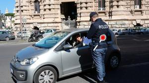 Sign of things to come: Police officers at a roadblock in Rome's city centre check whether motorists are respecting the quarantine and if they have a legitimate reason to travel