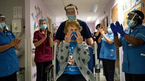 Margaret Keenan is applauded by staff at University Hospital Coventry as she returns to her ward after becoming the first person in Britain to get the Pfizer/BioNtech vaccine. Photo: Jacob King