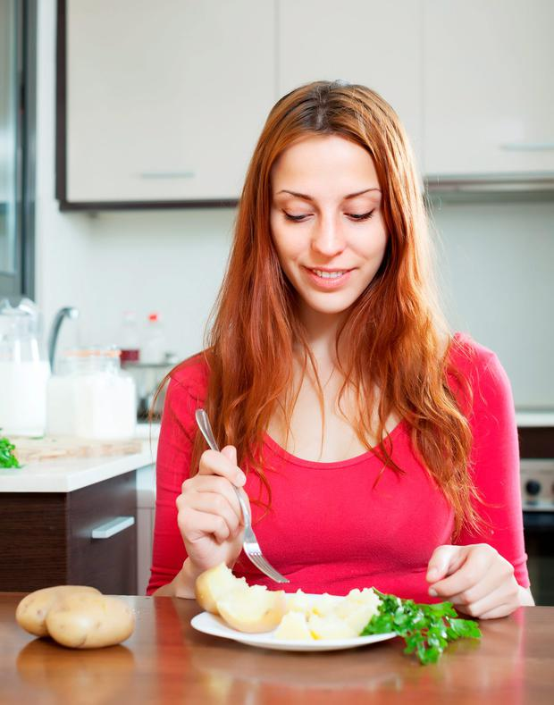 woman in red eating jacket potatoes at home