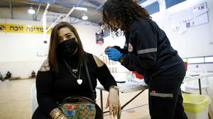 A woman is vaccinated against Covid-19 at a vaccination centre in Tel Aviv, Israel
