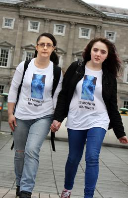 Linda Watts from Tuam, Co Galway, with her daughter Sophie O'Grady (14), who suffers from scoliosis, displaying a picture on their T-shirts of an X-ray of Sophie's spine at the protest by families at Leinster House yesterday