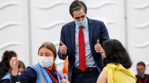 Higher Education Minister Simon Harris watching student nurse Sarah Dwyer give the vaccine to Eiham Zafarnia from Iran at Trinity College yesterday. Photo: Maxwells